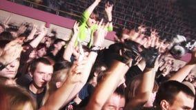 Gente que anima en el funcionamiento de la banda de rock en etapa en club nocturno proyectores Manos del aumento holidays metrajes