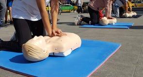 Gente que aprende cómo haga las compresiones del corazón de los primeros auxilios imagen de archivo