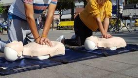 Gente que aprende cómo haga las compresiones del corazón de los primeros auxilios fotografía de archivo libre de regalías