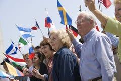 Gente que aumenta banderas de país diferente Imágenes de archivo libres de regalías