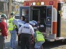 Gente que ayuda a poner en los hombres del enfermo de la ambulancia Fotografía de archivo
