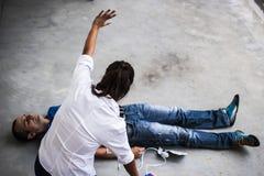 Gente que ayuda a un hombre inconsciente Fotos de archivo