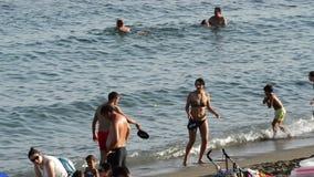 Gente que baña y que juega las paletas al borde de la playa una tarde del verano almacen de video