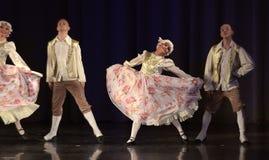 Gente que baila en trajes tradicionales en etapa, Foto de archivo