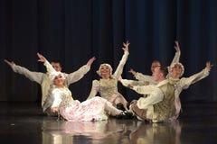 Gente que baila en trajes tradicionales en etapa, Imagen de archivo