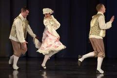 Gente que baila en trajes tradicionales en etapa, Fotos de archivo