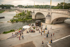 Gente que baila y que escucha la música debajo de un puente en una orilla Foto de archivo libre de regalías