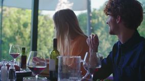 Gente que bebe, comiendo y hablando Cuatro amigos caucásicos hombre y ensalada de la mujer, filete italianos mediterráneos de la  metrajes