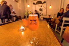 Gente que bebe la cerveza danesa popular por la cervecería de Mikkeller con diseño cómico brillante foto de archivo libre de regalías