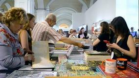 Gente que busca los nuevos libros, compras del libro, Kiev, Ucrania, almacen de video