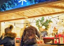 Gente que busca mercancías y recuerdos festivos en el mercado de la Navidad Foto de archivo