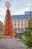Gente que camina alrededor del árbol de navidad de madera en Riga Foto de archivo