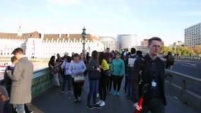 Gente que camina arriba y abajo del puente de Westminster, disfrutando de la vista del Támesis en un otoño soleado almacen de video