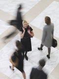 Gente que camina borrosa With Cellphone Amid sonriente de la empresaria imagenes de archivo