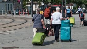 Gente que camina con la caja del traje delante de la estación de tren en Mulhouse Fotos de archivo libres de regalías