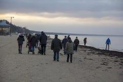 Gente que camina durante puesta del sol en Sandy Beach del mar Báltico foto de archivo libre de regalías