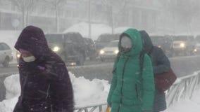 Gente que camina en ciudad durante la ventisca pesada, ciclón pacífico de la nieve almacen de video