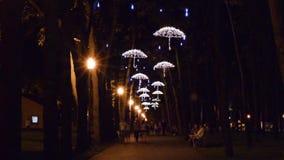 Gente que camina en el callejón y las lámparas del LED bajo la forma de paraguas en el parque por la tarde metrajes