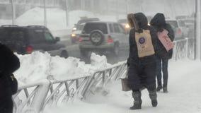 Gente que camina en la ciudad durante las nevadas pesadas, ciclón pacífico de la nieve metrajes