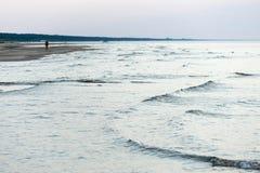 Gente que camina en la playa arenosa en puesta del sol Foto de archivo