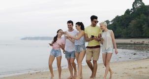 Gente que camina en la playa usando hablar en línea de los teléfonos elegantes de la célula, grupo joven de los turistas