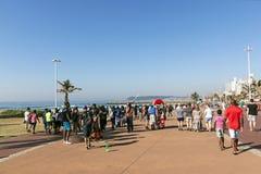 Gente que camina en la 'promenade' en frente de la playa Imagen de archivo libre de regalías