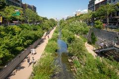 Gente que camina en las trayectorias a lo largo de una cala urbana fotografía de archivo libre de regalías