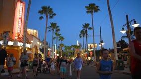 Gente que camina en Sunset Boulevard en fondo azul de la noche en Epcot almacen de video