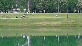 Gente que camina a lo largo de la orilla del lago Jarun en Zagreb almacen de video