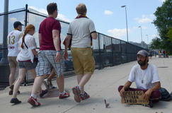 Gente que camina más allá de veterano sin hogar Imagen de archivo