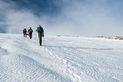 Gente que camina a través de las montañas nevadas Imagen de archivo