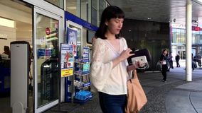 Gente que camina a través de las puertas en la tienda de London Drugs almacen de metraje de vídeo