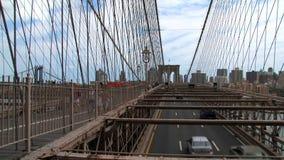 Gente que camina y conducción de automóviles en el puente de Brooklyn metrajes