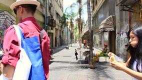 Gente que camina y que hace compras a lo largo de la calle muy transitada Asuncion en el grande bulevar de Sabana con el edificio metrajes