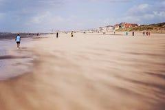 Gente que camina y que activa a lo largo de la playa contra los fuertes vientos que llevan la arena en la costa de Mar del Norte, fotos de archivo libres de regalías