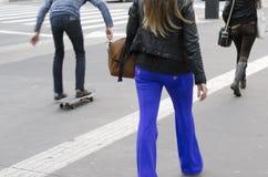 Gente que camina y que anda en monopatín en la calle Fotografía de archivo libre de regalías
