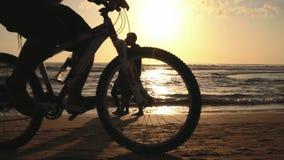 Gente que camina y que completa un ciclo en la playa en la puesta del sol metrajes