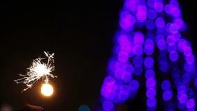 Gente que celebra Año Nuevo con las luces de Bengala en cuadrado central iluminado almacen de metraje de vídeo