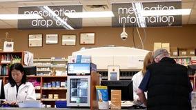 Gente que coge su medicina de la prescripción en la sección de la farmacia