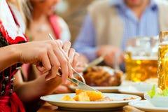 Gente que come el cerdo de carne asada en restaurante bávaro Imágenes de archivo libres de regalías