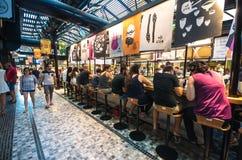 Gente que come en el nuevo mercado de la comida de Sarona en Tel Aviv, Israel Imágenes de archivo libres de regalías