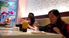 Gente que come la sopa de fideos y que lee el mensaje móvil metrajes
