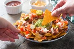 Gente que come los nachos mexicanos con carne de vaca, guacamole, salsa de queso, pimientas, el tomate y la cebolla en placa en l Imagen de archivo libre de regalías