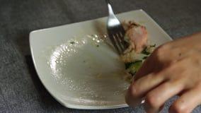 Gente que come los pescados de color salmón con arroz y el pepino almacen de metraje de vídeo