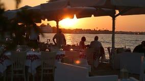 Gente que come y que bebe en el restaurante al aire libre de la playa de lujo almacen de video