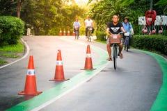 Gente que completa un ciclo en el parque Imagen de archivo libre de regalías
