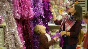 Gente que compra juguetes y malla de Navidad en el mercado de la Navidad, madre y niño que eligen la decoración festiva en la ala almacen de metraje de vídeo
