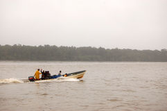 Gente que conduce el barco de motor de la velocidad en el río Imágenes de archivo libres de regalías