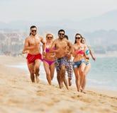 Gente que corre en la playa Imágenes de archivo libres de regalías