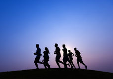 Gente que corre en la puesta del sol azul Foto de archivo libre de regalías